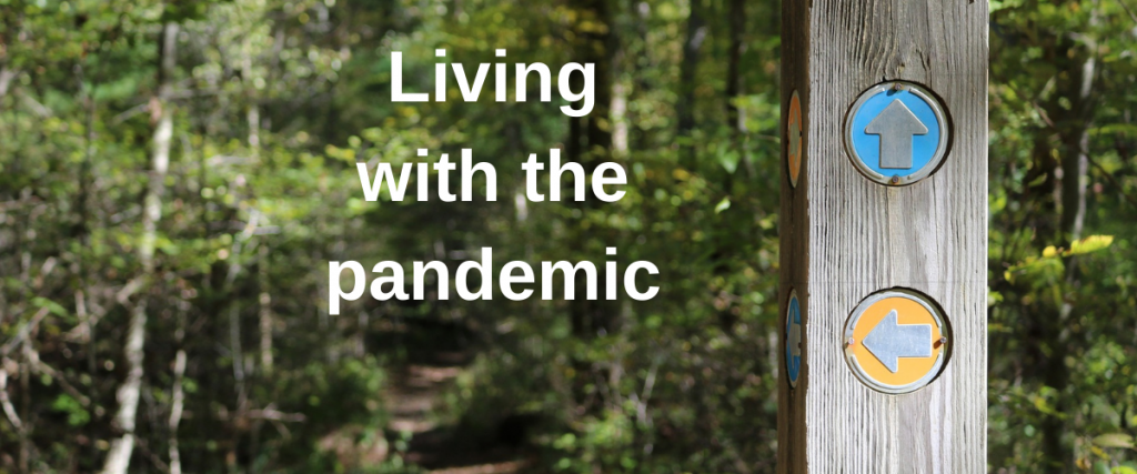 """Image of a post which has signs pointing in the direction of various paths within a woodland area. The text says """"Living with the pandemic""""."""