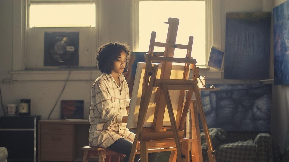 A woman sitting alone painting a canvas