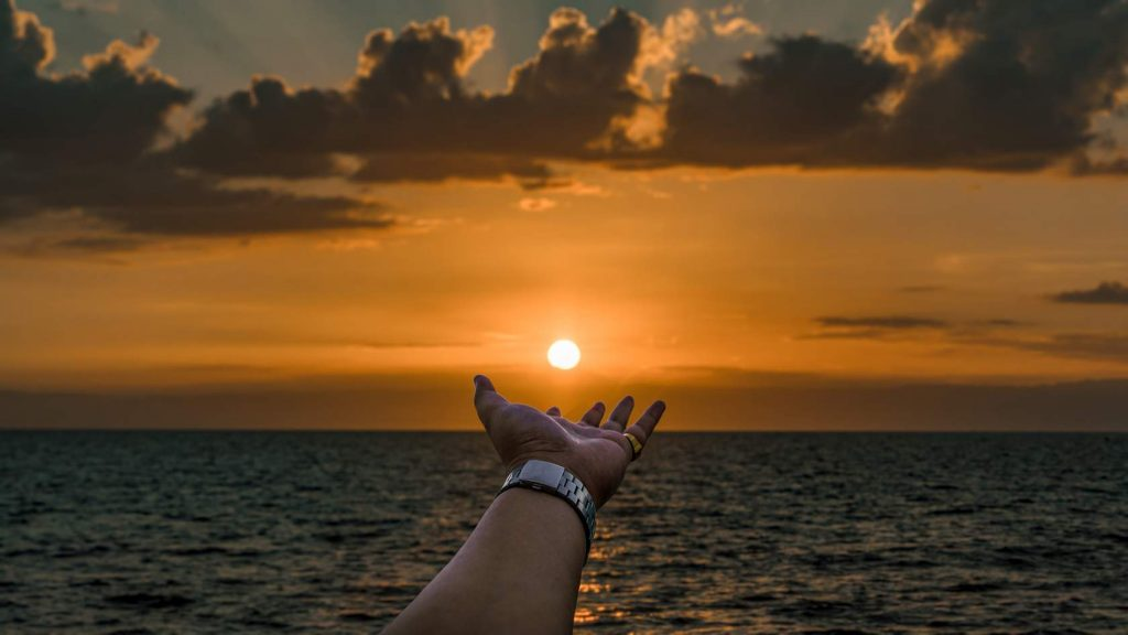 An orange sunset above the sea where the sun is low on the horizon and an arm reaches out below the sun as if it were holding the sun on the palm of its hand.