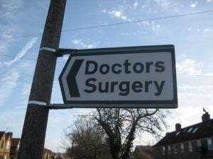 A sign directing to a doctors surgery