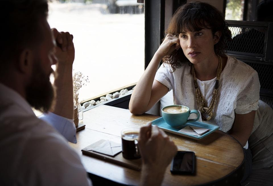 A man and a woman sitting in a café talking with a cup of coffee