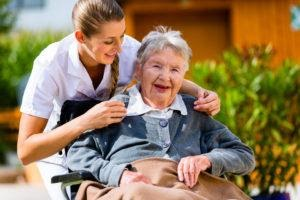 A healthcare assistant comforting an elderly patient