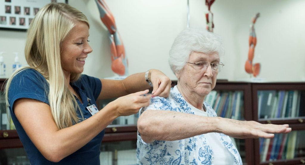 An occupational therapist working with an elderly patient