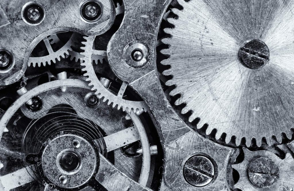 A black and white photo of a series of metal cogs and springs.
