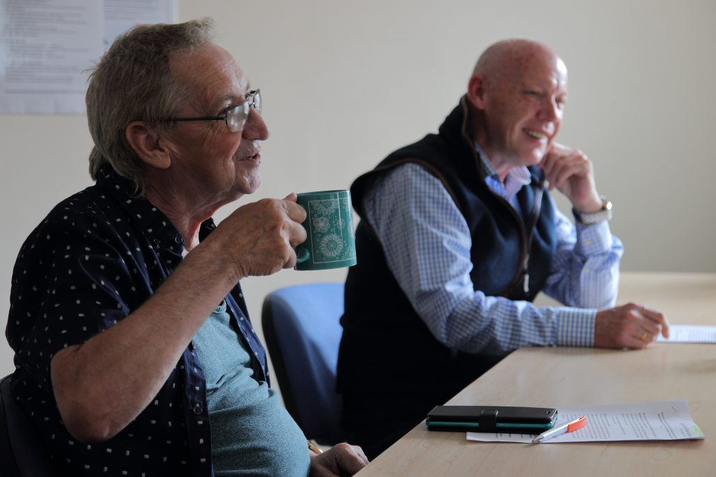 Image of two men chatting together in a classroom and looking happy.