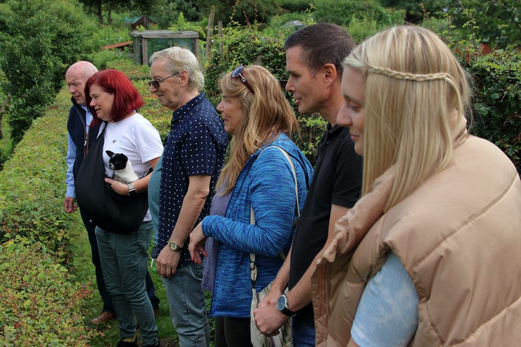 Group of people on a mindful walk looking at a garden.