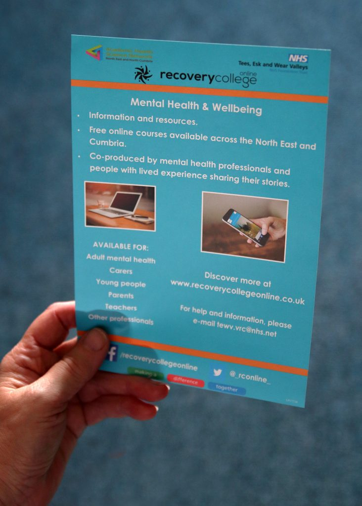 Image of a hand holding a Recovery College Online information flyer.