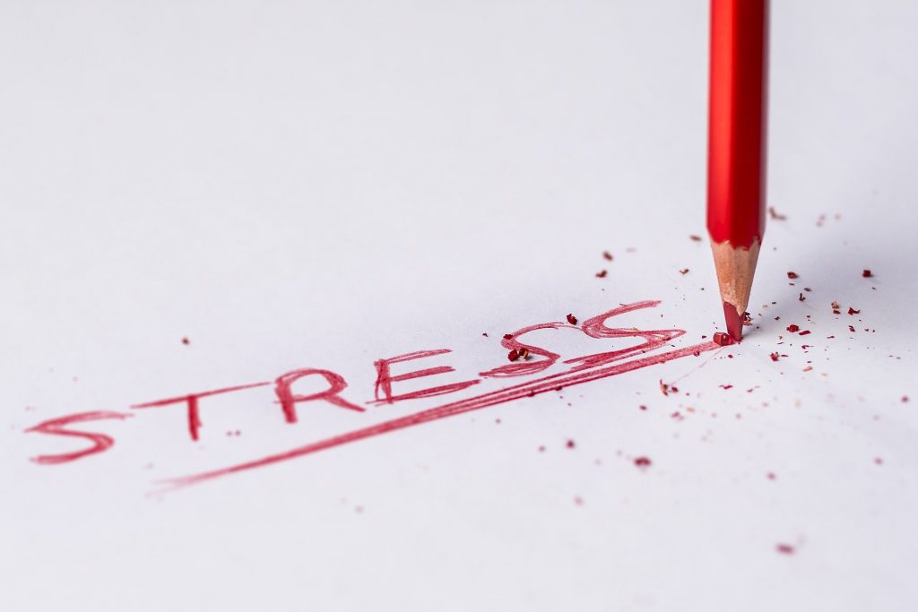 Image of a red pencil writing the word stress on paper.
