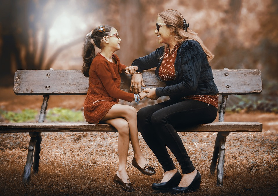 A woman and a child sat together on a park bench in autumn smiling at each other and holding hands.