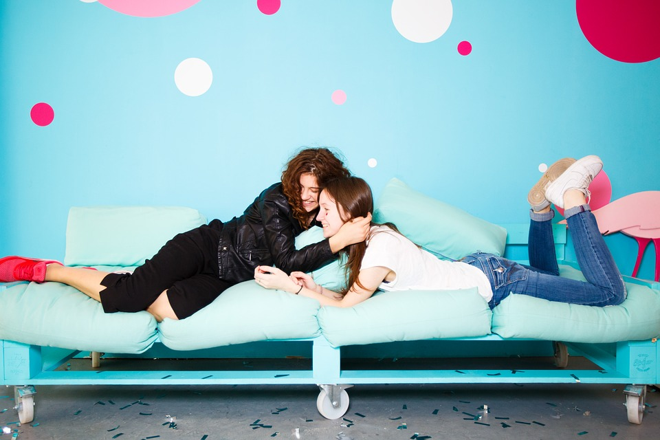 Two teenage girls on a sofa hugging and smiling with a pale blue background that has a variety of pink and white dots.